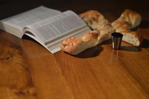 Bread in the shape of a cross with an open bible and a goblet of wine with spilled wine