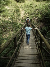 Father and son walking over a wooden bridge,