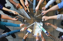 volunteers standing in a circle their hands holding tools as a symbol for: working together to fix things in the church building.