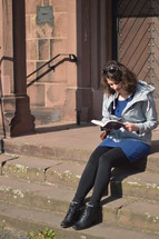 a woman reading a Bible on church steps