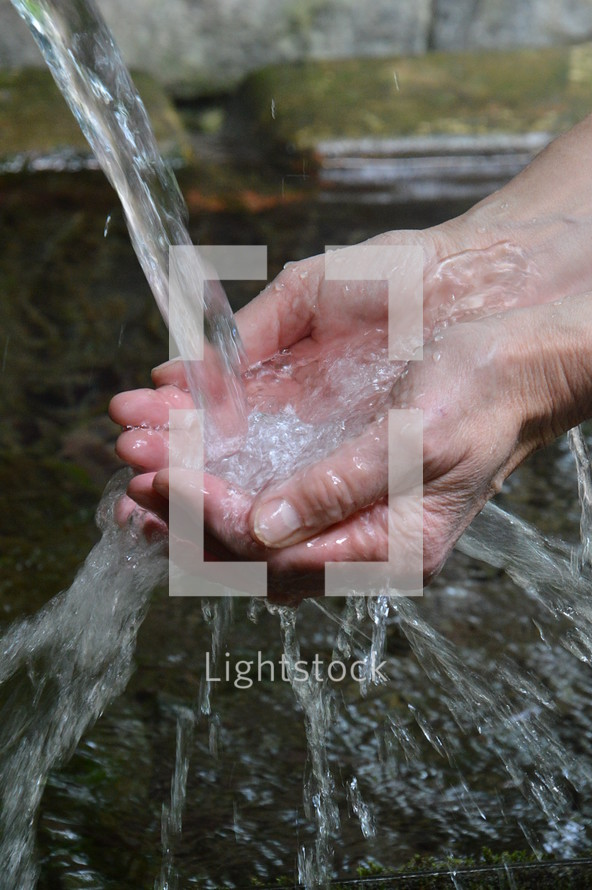 Hands overflowing with streams of water.