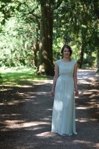 a woman in a vintage dress standing on a path in a forest