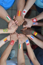 International brothers and sisters in Christ standing in a circle together and holding hands.