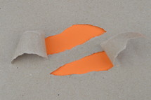 ripped paper revealing orange blank space for words