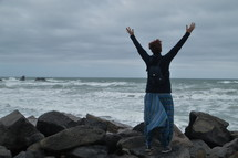 a woman with raised hands standing on a rocky shore