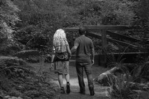 a couple walking holding hands in a park  - on the way as a couple.