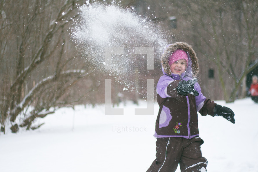 a girl child throwing a snowball