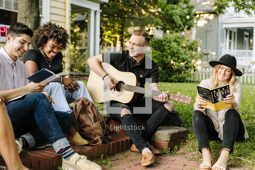 man playing a guitar outdoors at a Bible study