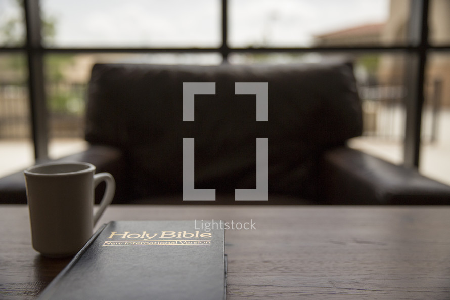Holy Bible and coffee mug on a table in front of a window