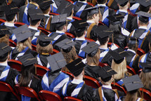 Students in caps and gowns at a graduation ceremony.