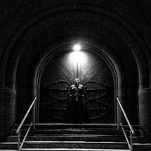 Man on church front steps, underneath light