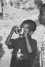 child taking a photograph