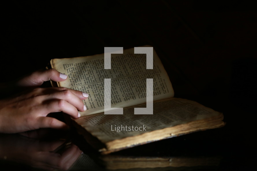 hands on an open Bible