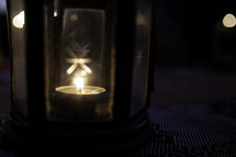 votive candle glowing in a glass lantern