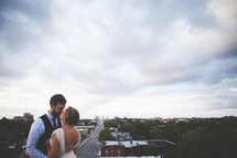 Husband and wife kissing on rooftop