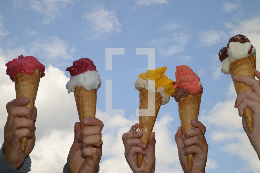 hands holding up ice cream cones