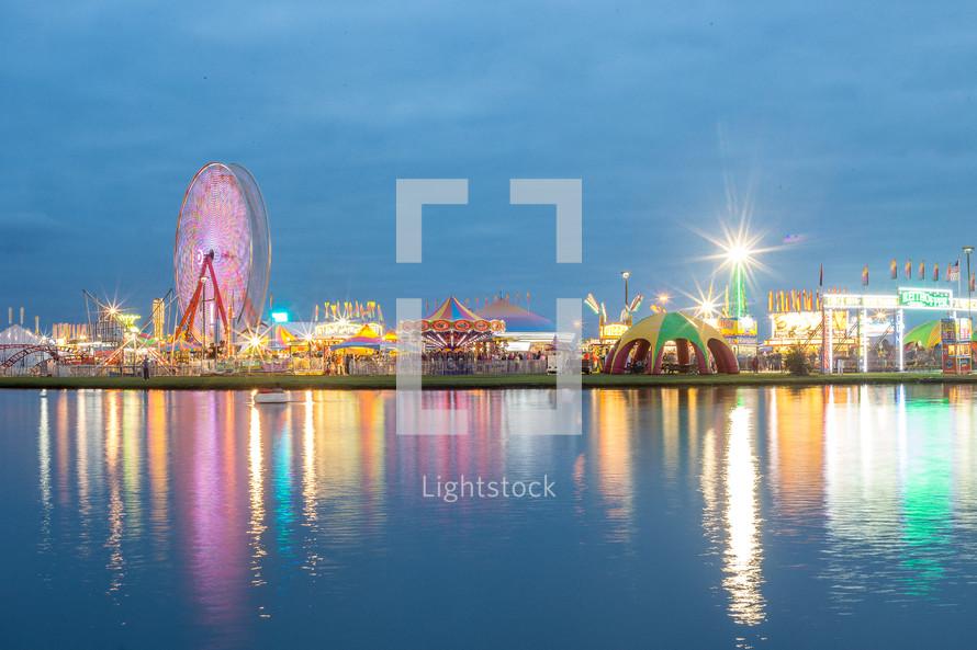 amusement park lights along a shore