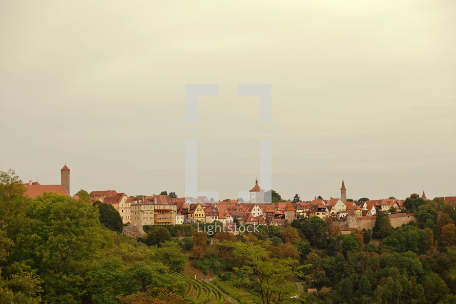 Homes and churches on tree-covered hill top.