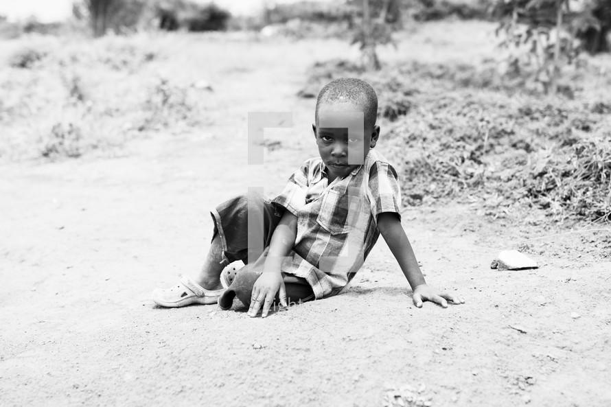 a little boy sitting on the ground
