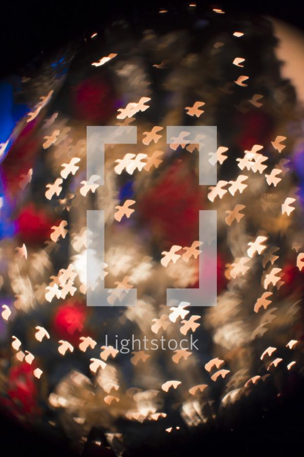 Close up of illuminated white doves on Christmas tree.