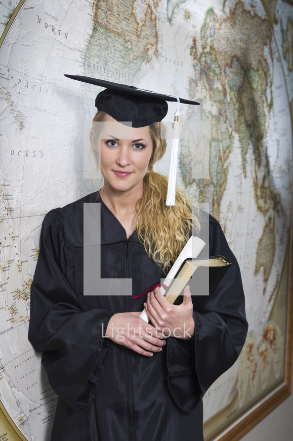 college student standing in her cap and gown at graduation
