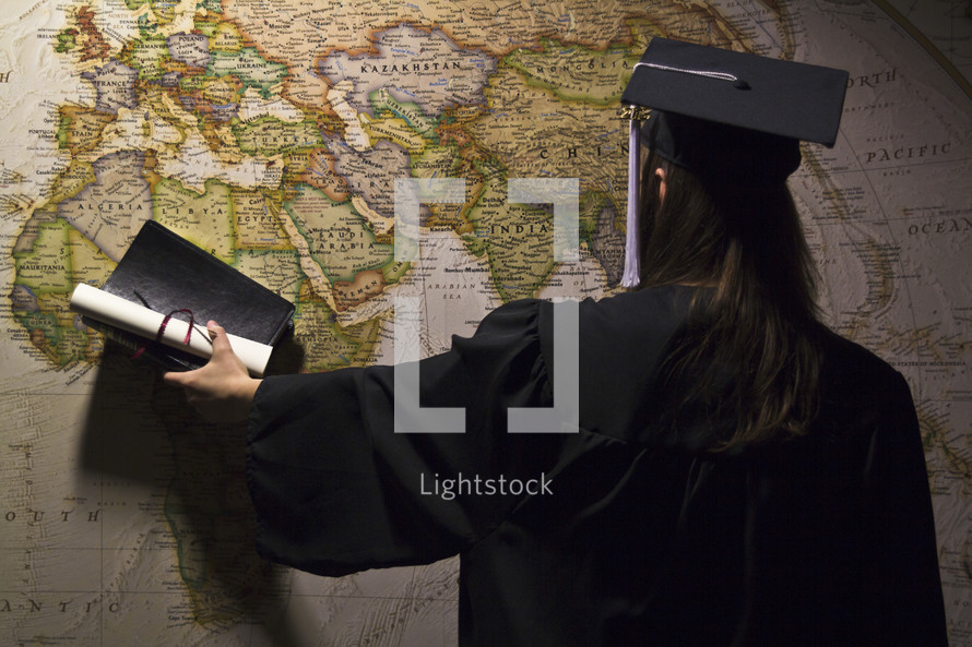 graduate pointing to a world map in her cap and gown
