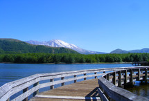 Walking bridge over a lake with Mt. St Helens Volcano in the background