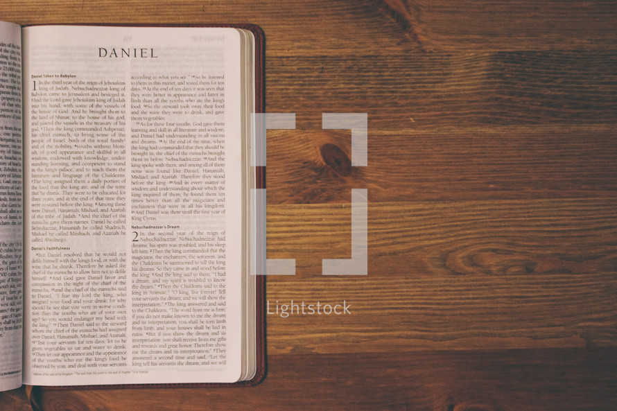 Bible on a wooden table open to the book of Daniel.