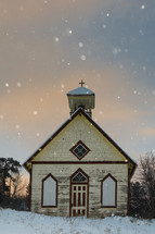snow falling around a rural church