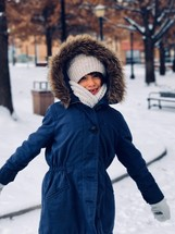 a girl in a coat in snow