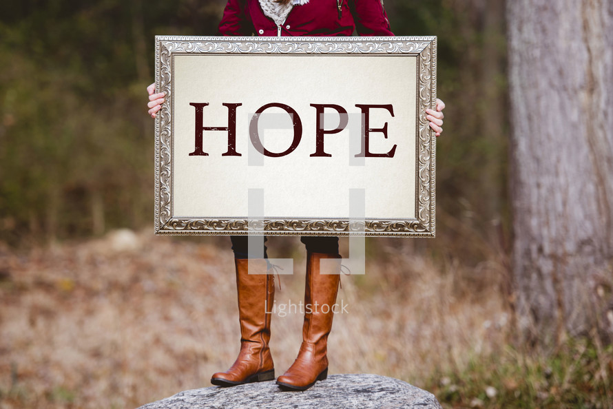 a woman holding a sign the reads hope