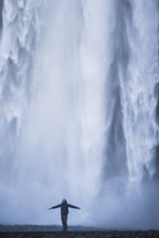 a man standing with open arms in front of a waterfall