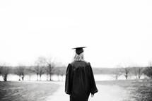 female graduate walking on a dirt road
