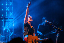 A musician on stage with arm raised lifted worship leader passion guitar pointing up finger