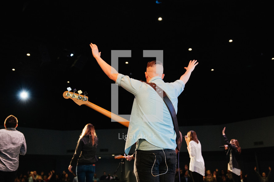 a musician on stage with hands raised in the air