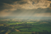rays of sunlight from clouds above a green landscape
