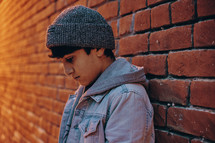 a boy leaning against a brick wall looking down