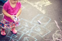 Aerial view of toddler girl in pink shirt with sidewalk chalk in her hands standing on sidewalk with chalk drawings on it.