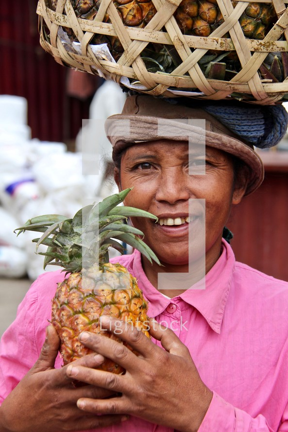 a woman holding a pineapple with a basket on her head