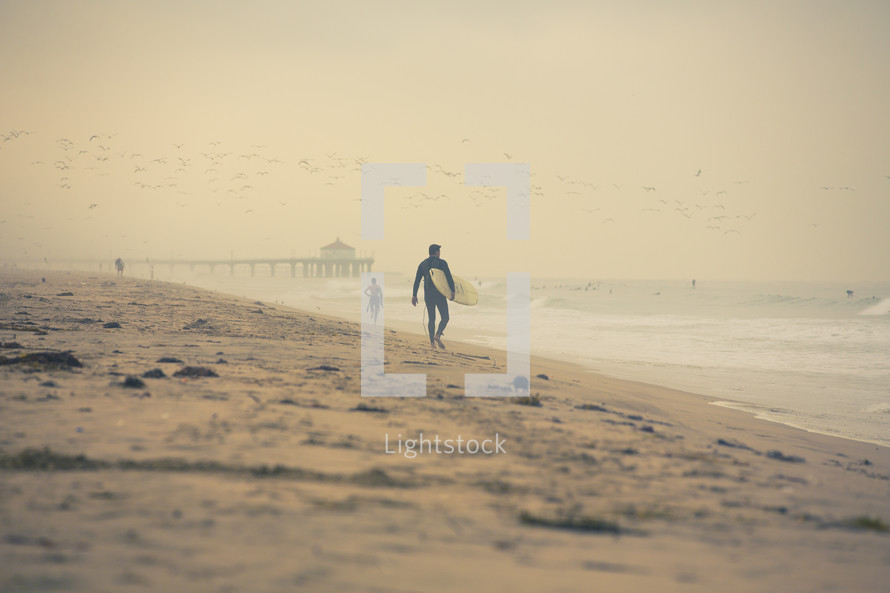 surfer walking down the beach holding a surf board