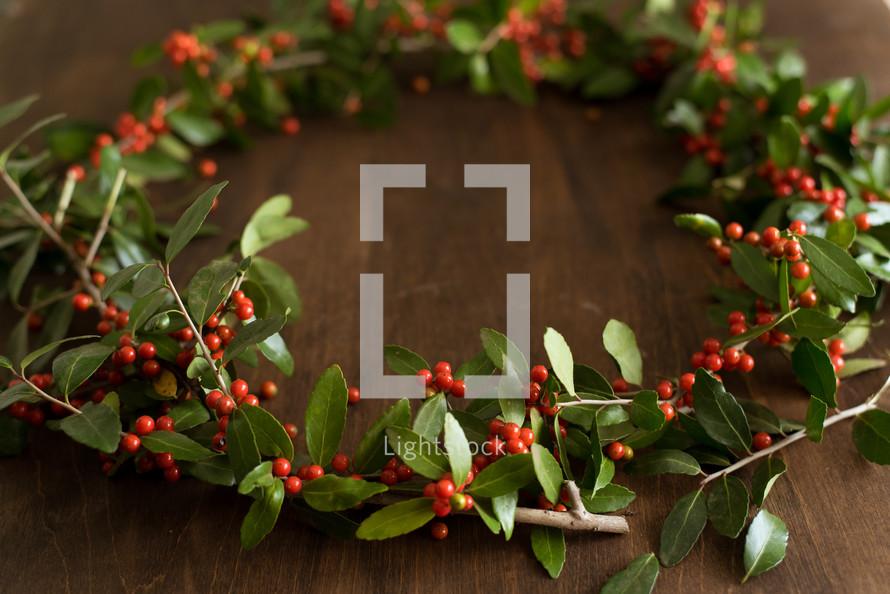 a holly wreath on a wood table