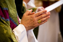 hands of a priest in prayer