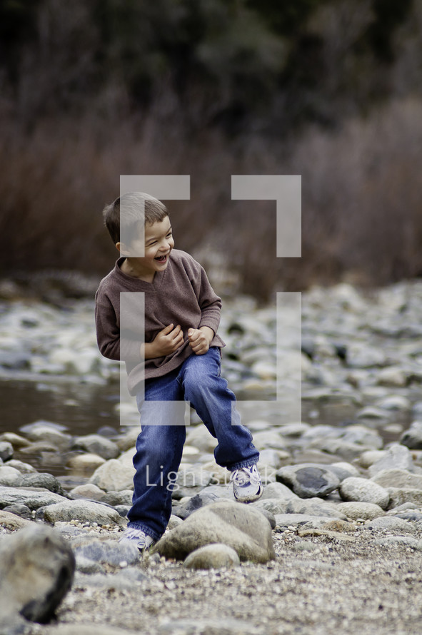 little boy laughing outdoors