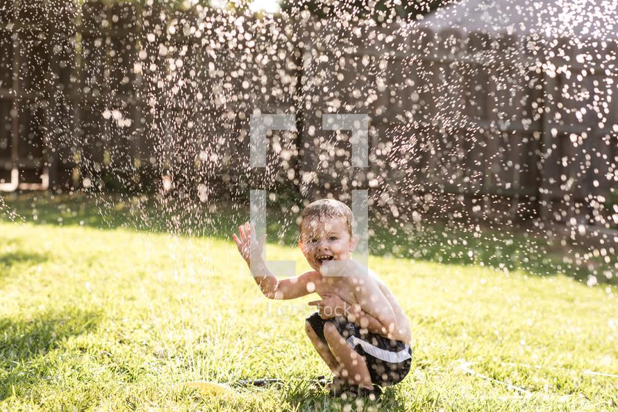 boy playing in a sprinkler
