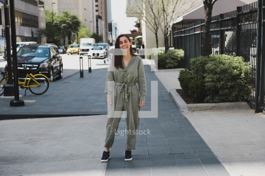 smiling woman standing on a downtown sidewalk