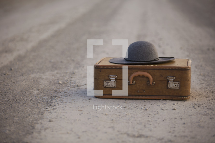 a suitcase and hat on the road