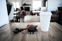 car keys, cellphone, wallet, and coffee cup on a cafe table