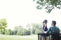 father and daughter sitting on a park bench outdoors