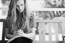 woman sitting on a porch swing praying with a Bible in her lap