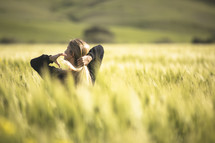 a woman putting her hair in a ponytail standing in a field of wheat